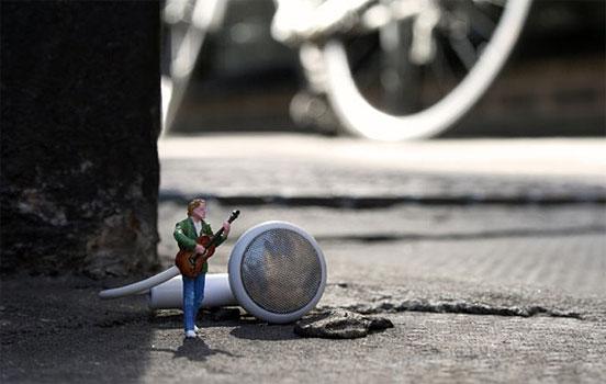 Pequenina escultura de uma pessoa tocando guitarra com a caixa de som sendo o falante de um headfone