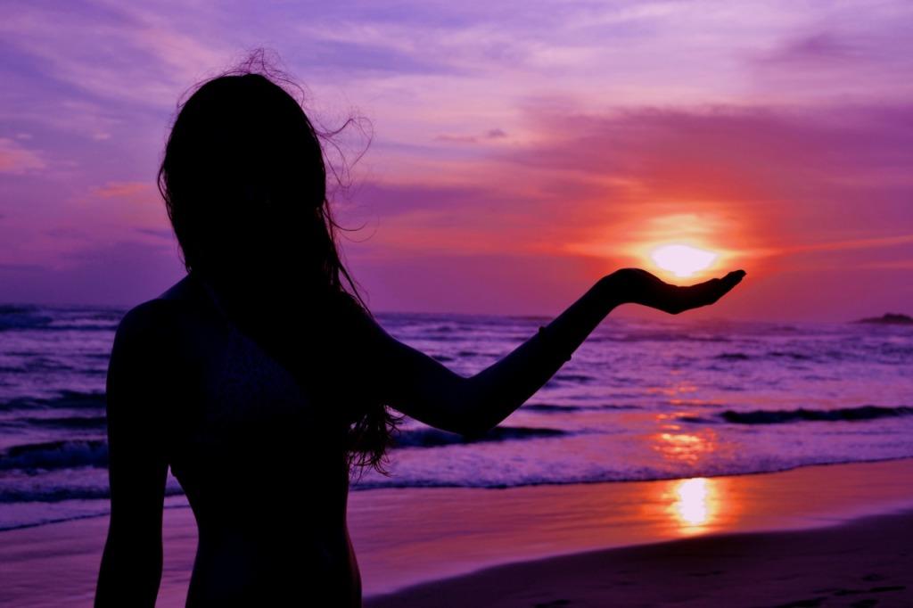 mulher vista de cintura pra cima e de frente mas no contraluz na beira do mar com a mão como se segurasse o Sol que se apoia na palma antes de se por no mar