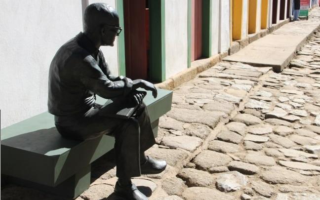 Estátua do poeta Carlos Drummond sentado em um banco em Paraty