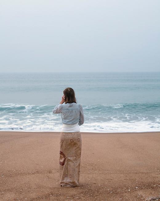 Foto de uma mulher numa praia na areia olhando pro mar, usando uma saia cor de areia e uma blusa cor de espumas e de mar