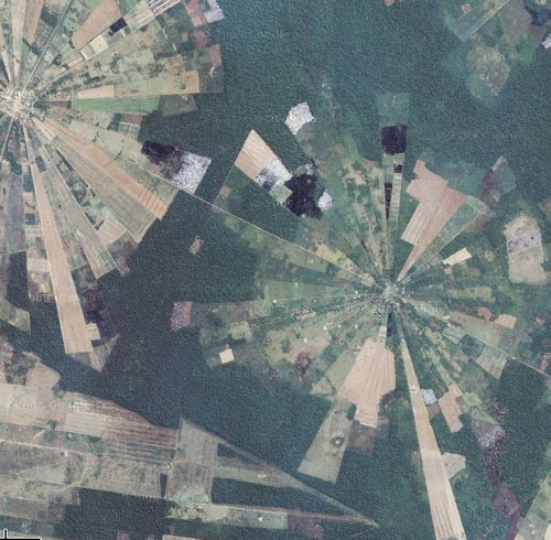 Vista aérea (do espaço) de grande área verde e urbana circular dividida como uma pizza, em fatias de textura