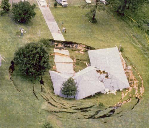 Vista aérea de casa onde o terreno inteiro cedeu formando uma área circular afundada no terreno
