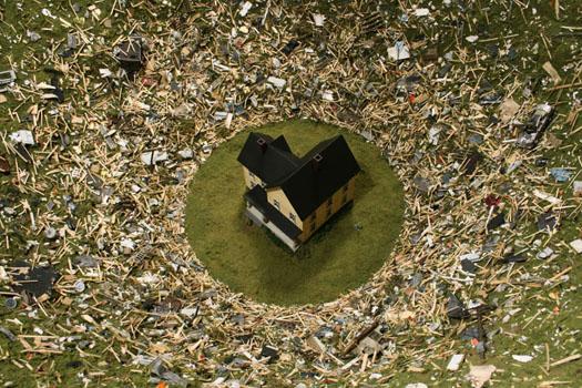 Casa vista de cima com pequena área verde circular em volta e rodeada de lixo ao redor dessa área