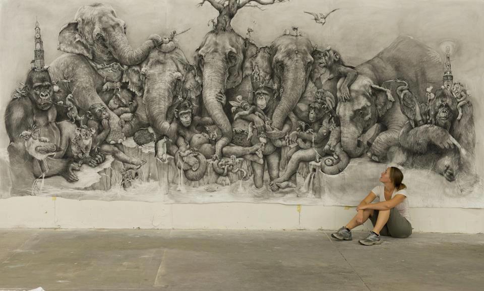 Foto de uma parede toda desenhada com grafite hiperralista com vários elefantes, macacos, etc, e a artista jovem sentada ao lado