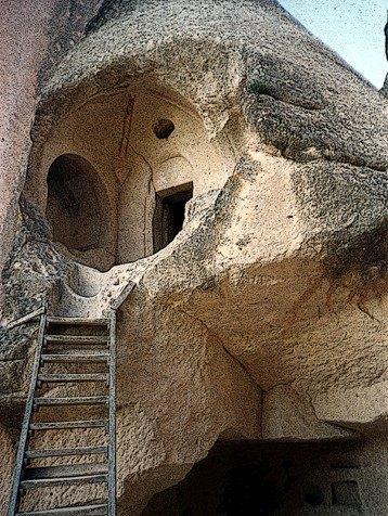 Esdada de madeira levando a uma casa escavada na pedra