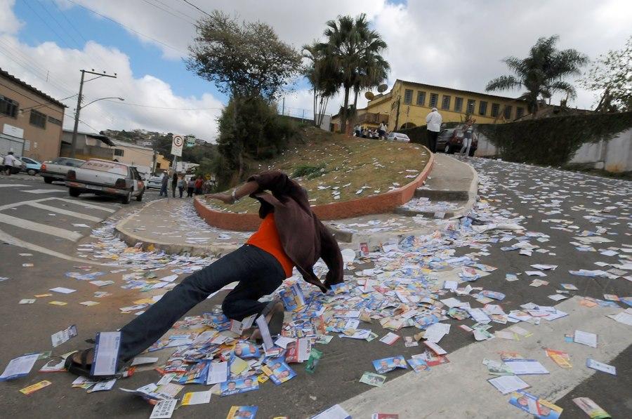 Foto com pessoa escorregando em uma ladeira cheia de propaganda eleitoral
