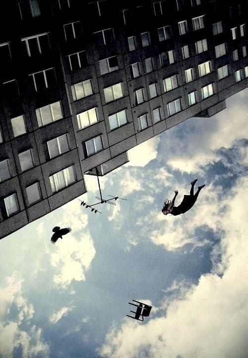 Foto de cabeça pra baixo com uma mulher flutuando junto com uma cadeira e um pássaro no céu da cidade
