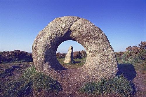 Rocha circular com um furo no meio através do qual se vê outro rocha pontuda ao fundo, com céu azul e claro por cima