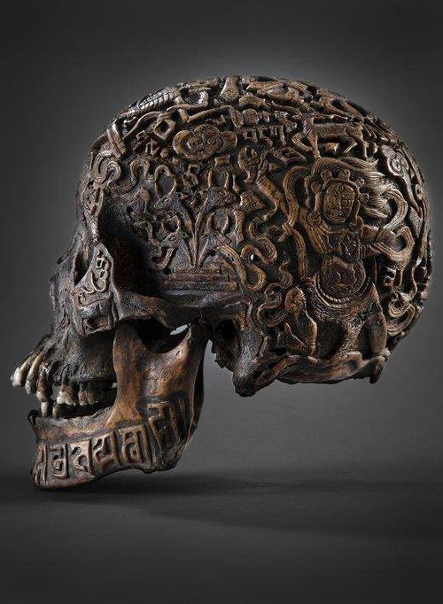 Cranio realista de madeira escura decorado com padrões circulares e figuras de seres