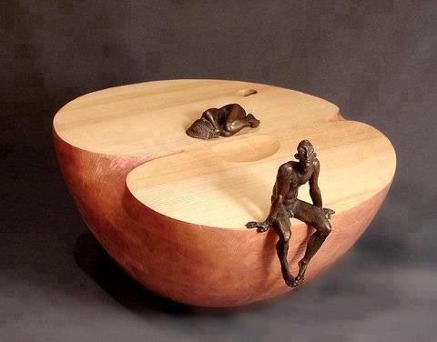 Escultura de uma metade de maça cujas sementes são uma mulher dormindo e um homem que acabou de acordar, sentado em sua borda