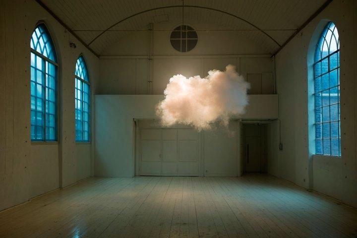 Sala vazia com janelas laterais e uma nuvem de verdade flutuando, suspensa pouco abaixo do teto