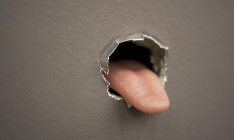 Buraco na parede de onde sai uma lingua humana