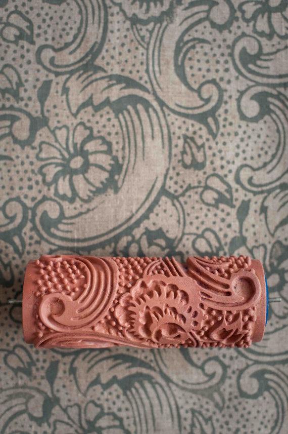 Rolinho de pintar parede com textura barroca aplicada em frente a parede coberta com a textura