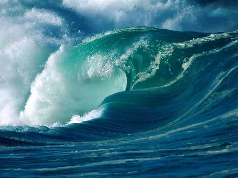 Onda quebrando e formando uma concha de água em movimento e ao fundo um ceu azul com nuvens