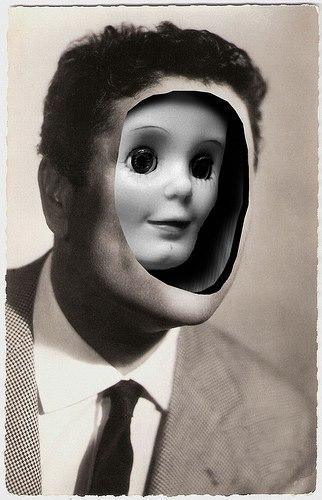 Foto antiga mostrando um homem de terno com a face cavada e dentro e menor o rosto de um boneco