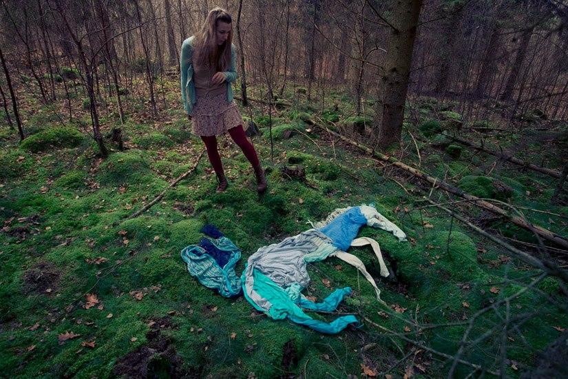 Foto de uma mulher na floresta olhando no chao um unicornio feito de roupas deitado no chao