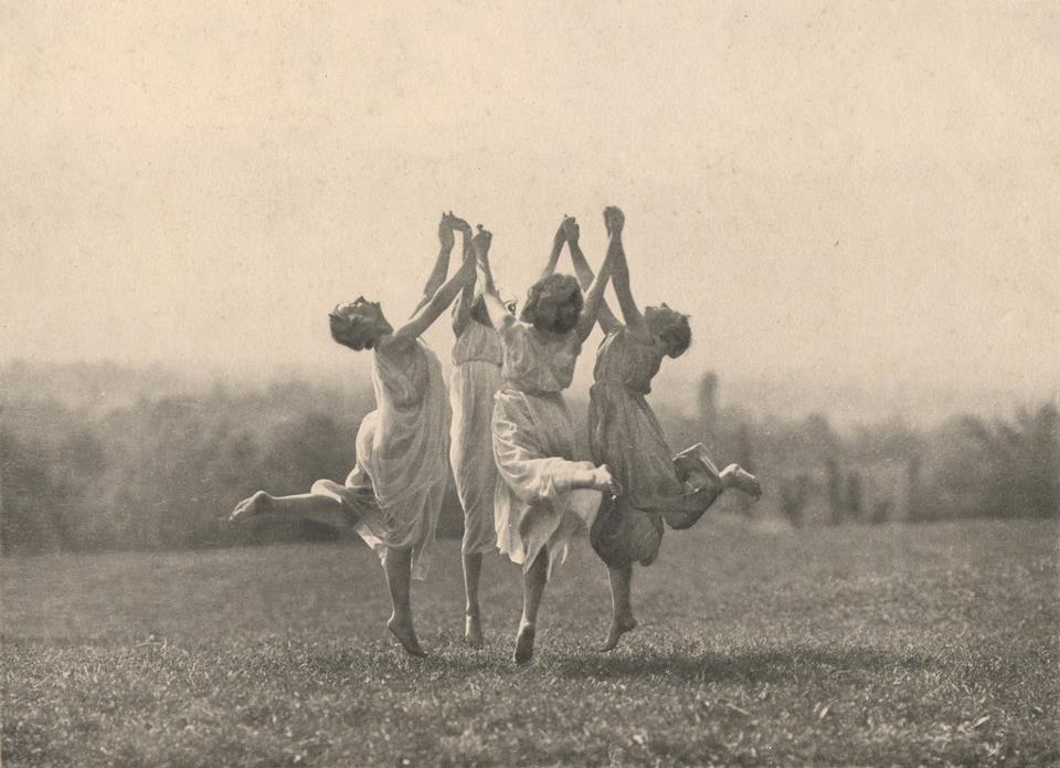 tres mulheres dançando com as mãos unidas no alto