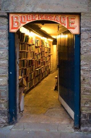 Foto de uma porta larga em arco escrita passagem dos livros em francês, e dentro pratelerias com livros nas paredes