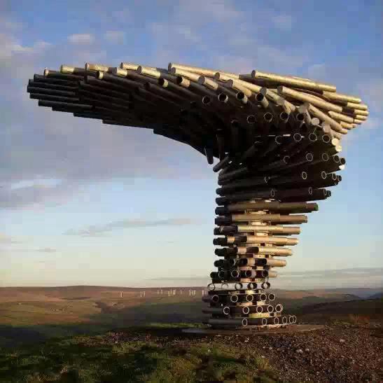 Escultura de canos em espiral que emite sons conforme o vento, em um campo aberto