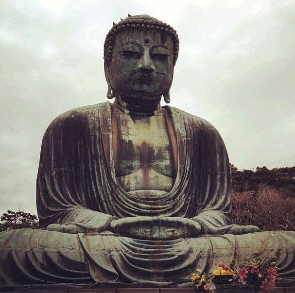 Foto do Buda gigante sentado meditando com flores em vasos à frente e uma colina aberto atrás com poucas árvores