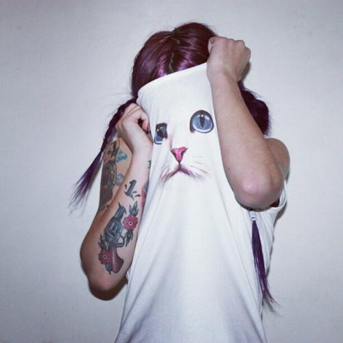 Garota tatuada com o rosto coberto por uma camiseta branca com a face de um gato estampada