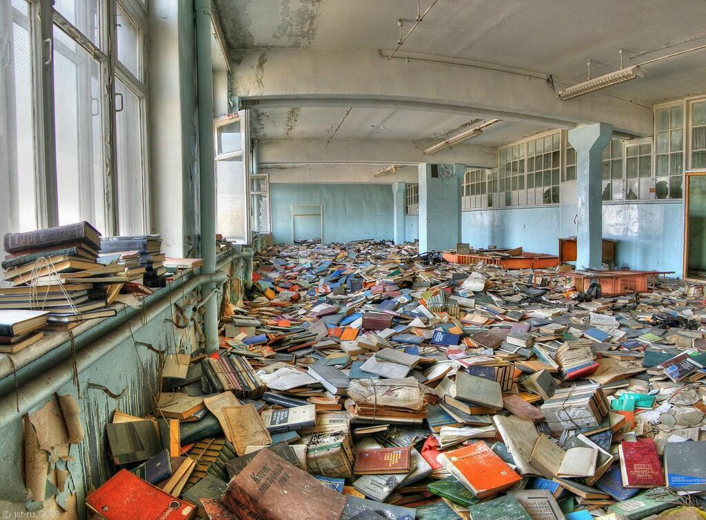 Amplo lugar abandonado com lmuitos livros espalhados no chão