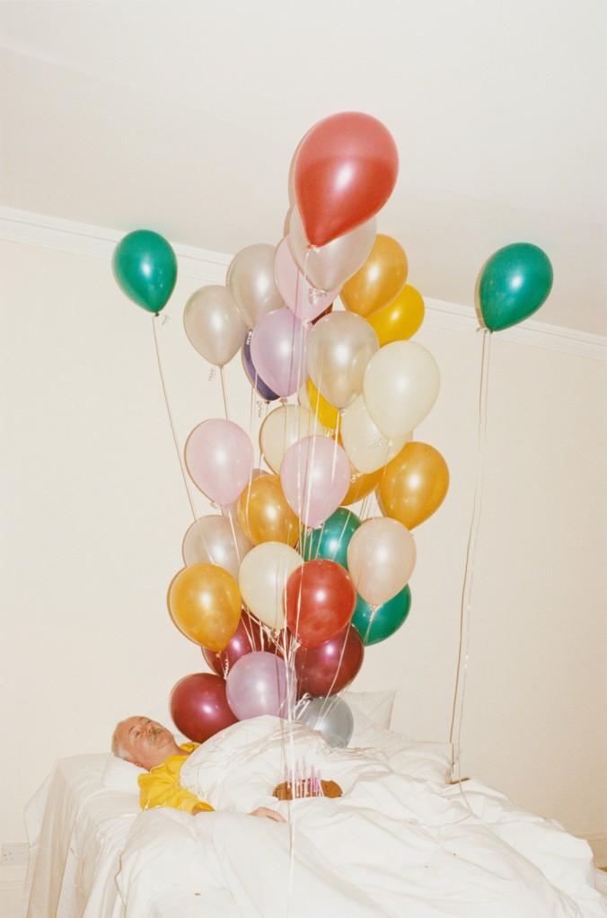 Senhor domindo em uma cama branca com balões coloridos saindo dele