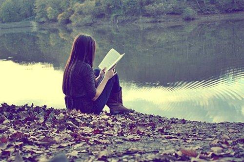 Menina de cabelo liso, de calça comprida, sentada em frente a um rio, lendo