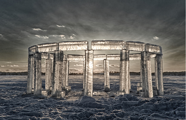 in a vast frozen open landscape an architectural circle of ice blocks resemble the stonehenge and reflect the light of the sun behind